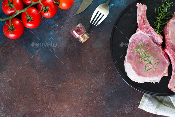 Raw lamb ribs marinating with buna-shimeji and tomato in a grill pan on a dark stone background with - Stock Photo - Images