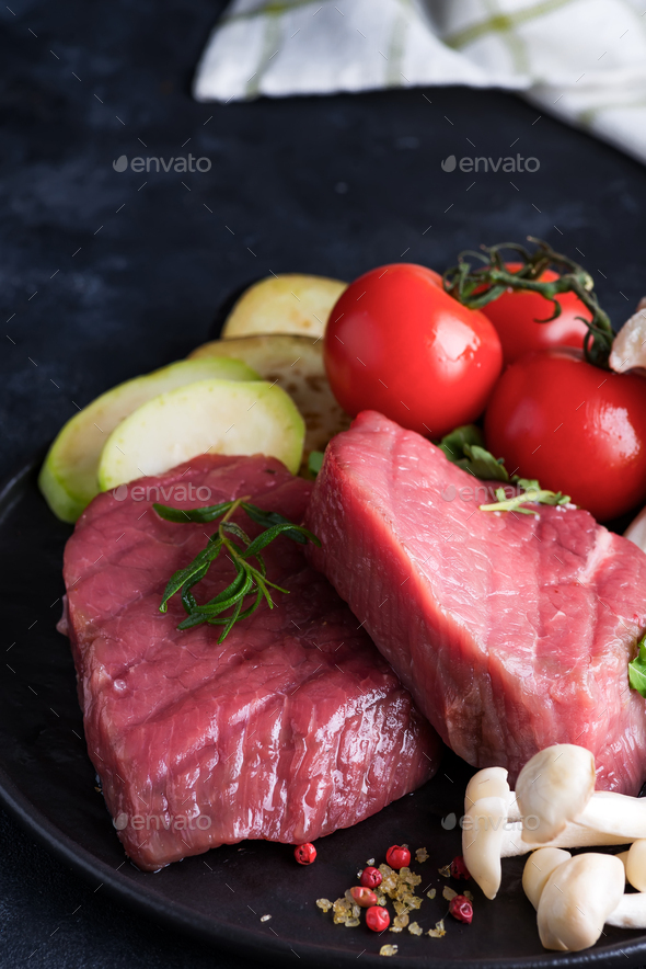 Raw beef steak on the bone with fresh vegetables in a pan on a dark stone background - Stock Photo - Images