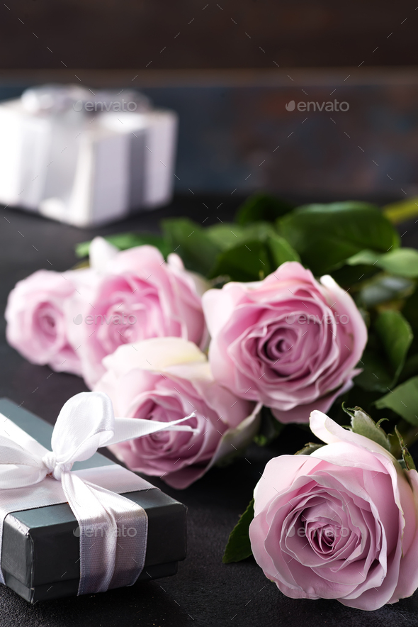 Pink roses and a gift box on a stone background. Vintage style, retro interior with flowers. Space - Stock Photo - Images
