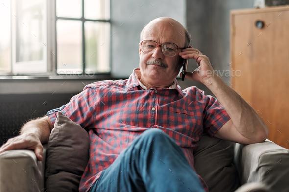 Retired hispanic man talking on phone sitting at living room. - Stock Photo - Images