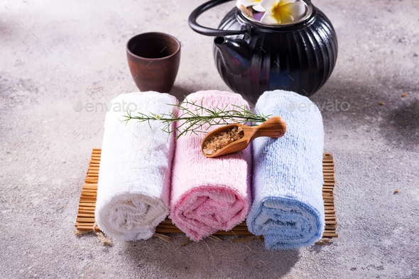 Color towels with green leaves, spoon of salt and detox tea on bamboo mat and stone table - Stock Photo - Images