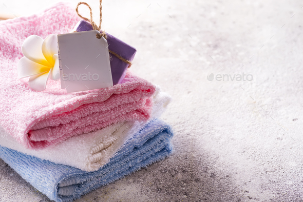 Lots of colorful bath towels stacked on each other with hand soap and flower on light stone - Stock Photo - Images
