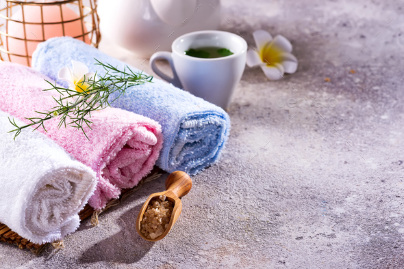 Wellness setting. Sea salt , towel, tea and flowers on stone background. Space for copy - Stock Photo - Images