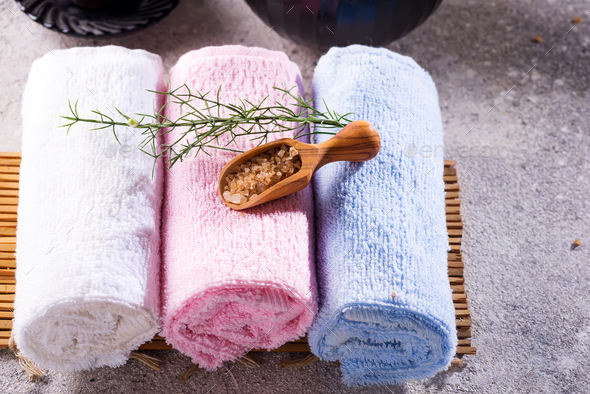 Color towels with green leaves and a spoon of salt on bamboo mat and stone table - Stock Photo - Images