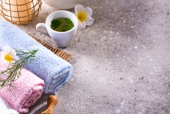 Color towels with flower, spoon of salt, on bamboo mat, bath spa treatment and green tea on stone - Stock Photo - Images