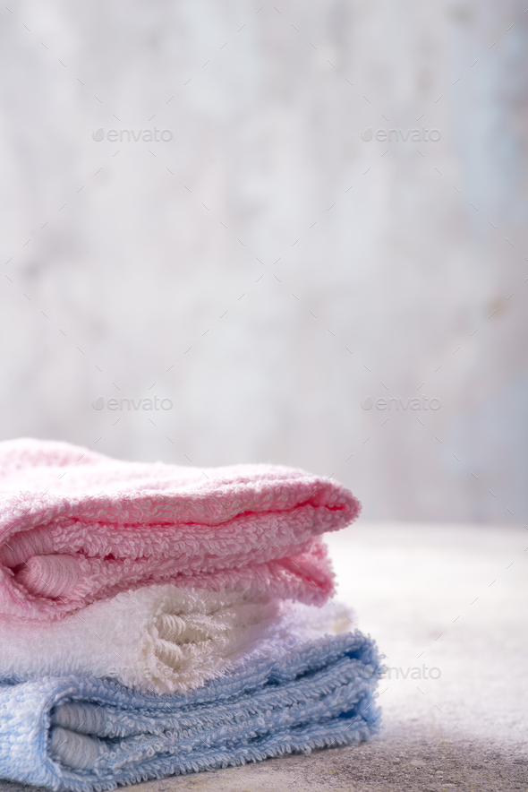 Lots of colorful bath towels stacked on each other on light stone background, copy space - Stock Photo - Images