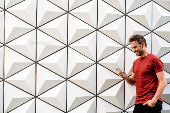 Man with mobile phone leaning on the wall - Stock Photo - Images