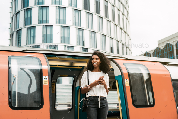 Black woman using mobile phone at london underground - Stock Photo - Images