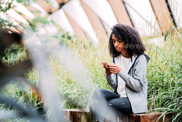 Woman sitting in a beautiful garden using mobile phone - Stock Photo - Images