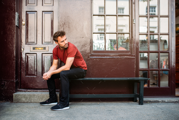 Man sitting in a bench on a beautiful maroon background - Stock Photo - Images