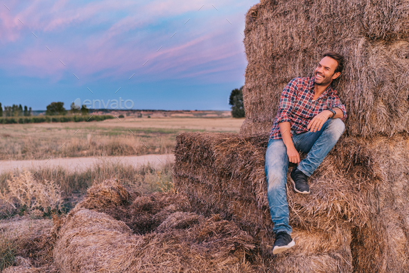 Happy man sitting on a pile of hay - Stock Photo - Images