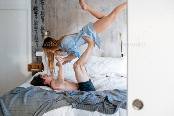 couple playing and having fun at home on bed - Stock Photo - Images