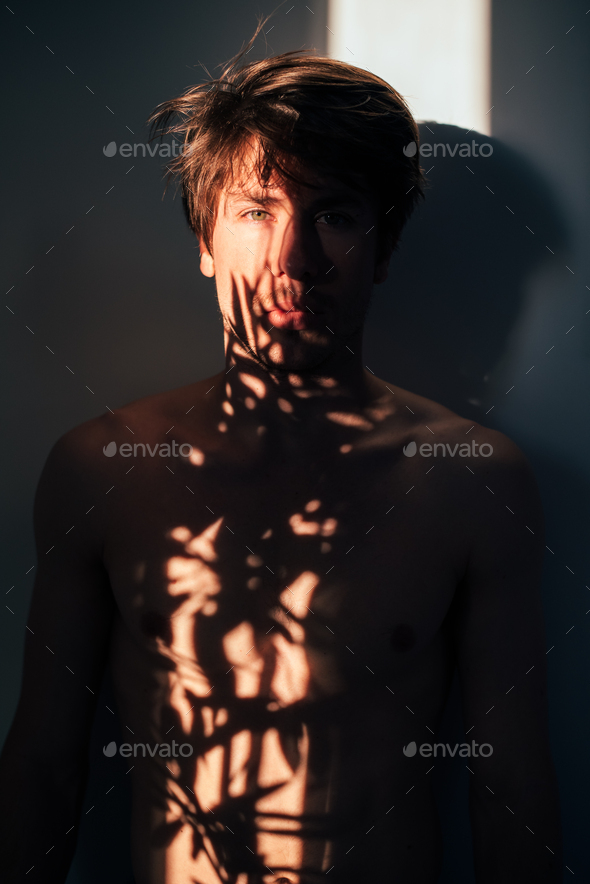 Man standing near plant with shadow light - Stock Photo - Images