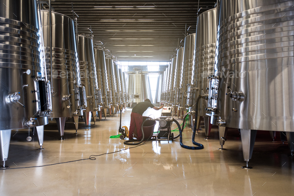 Man in a winery working in the wine process - Stock Photo - Images