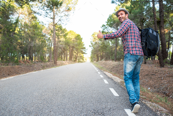 Man hitchhiking with thumbs up in a countryside road - Stock Photo - Images