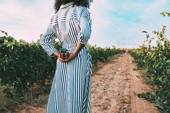 Young woman walking in a path in the middle of a vineyard - Stock Photo - Images