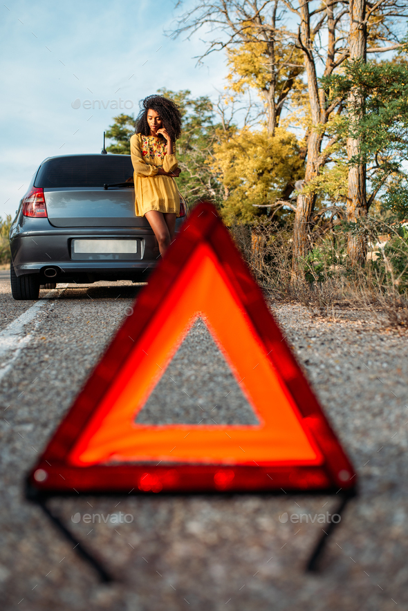 Woman with broken car and triangle - Stock Photo - Images