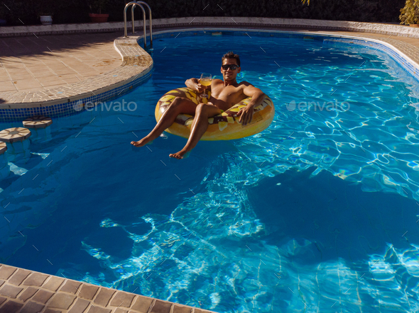 man on beach mat in swimming pool of a villa house - Stock Photo - Images