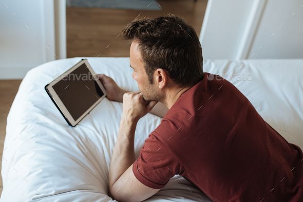 Man lying down on bed with tablet - Stock Photo - Images