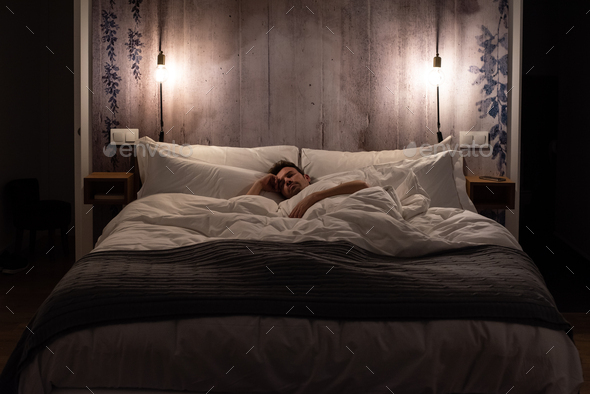 Man sleeping in bed in a modern beautiful bedroom - Stock Photo - Images