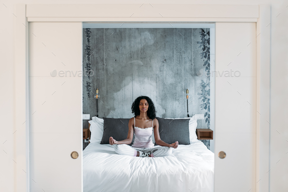 Attractive black woman on bed meditating - Stock Photo - Images