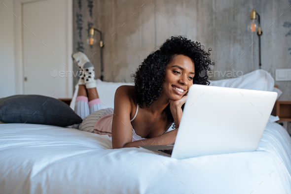 Woman sitting on bed on the computer - Stock Photo - Images