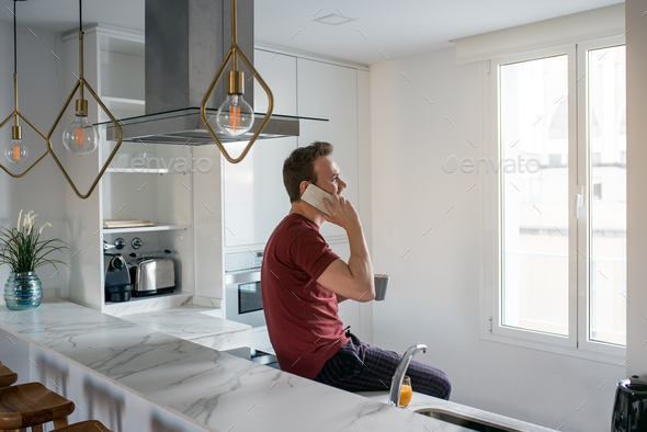 Man having breakfast with mobile phone - Stock Photo - Images
