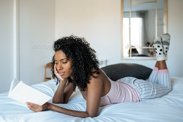 Woman lying down on bed reading a book - Stock Photo - Images
