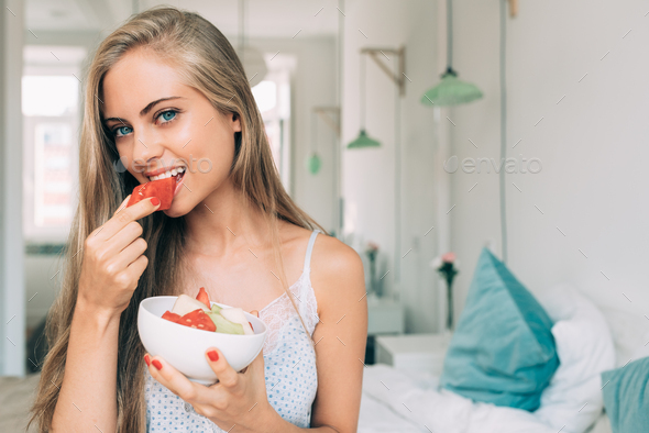 Young healthy beautiful blonde woman in the bed eating fruits - Stock Photo - Images