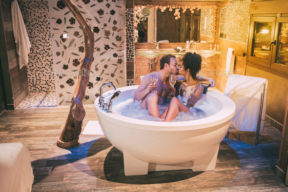 Happy interracial couple relaxed in the jacuzzi enjoying their self and drinking wine - Stock Photo - Images