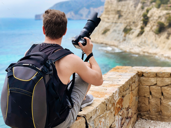 Photographer taking a picture of a ocean coast - Stock Photo - Images