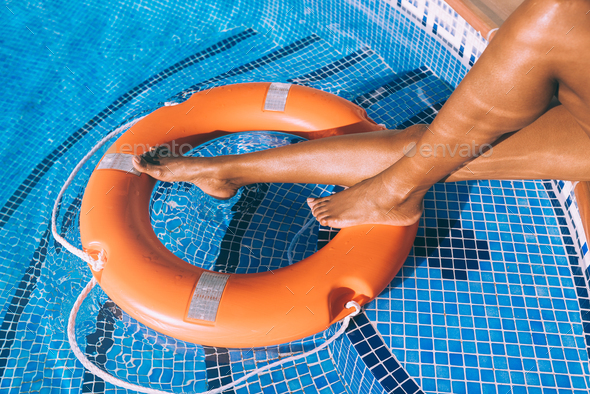 Woman legs in a swimming pool with lifesaver - Stock Photo - Images