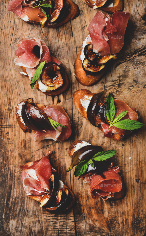 Crostini with prosciutto, goat cheese and grilled figs on board - Stock Photo - Images