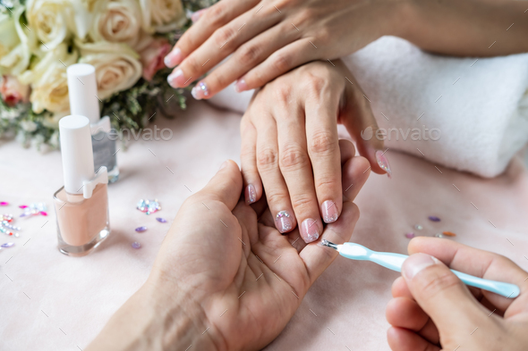 Beautiful manicure nails paint with glitter and gems in nail salon - Stock Photo - Images