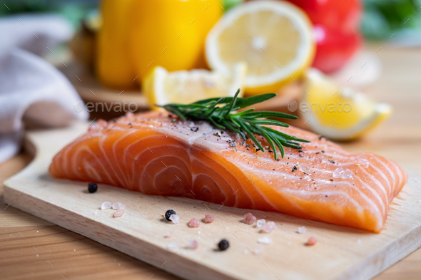 Fresh salmon steak with herbs, lemon and ingredients for cooking in kitchen - Stock Photo - Images