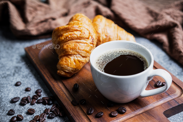Breakfast with fresh croissants and cup of black coffee on wooden board - Stock Photo - Images