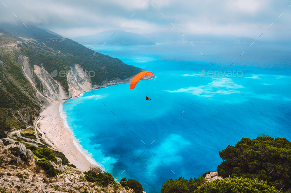 Aerial view of the paraglider flying over gorgeous Myrtos beach. Amazing water colors and beautiful - Stock Photo - Images