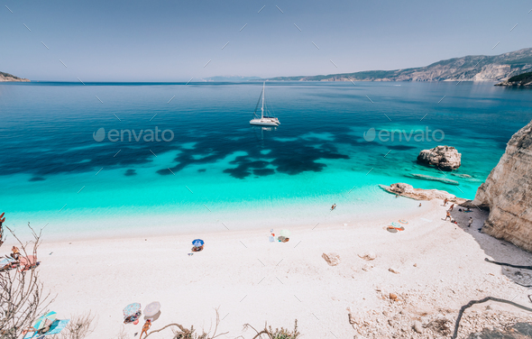 Azure water of Fteri beach, Cephalonia Kefalonia, Greece. White catamaran yacht in clear blue sea - Stock Photo - Images