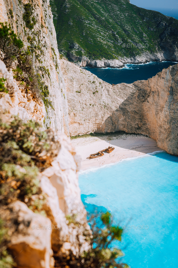 Navagio beach. Pure turquoise azure cyan teal blue sea water surrounded by huge white limestone - Stock Photo - Images