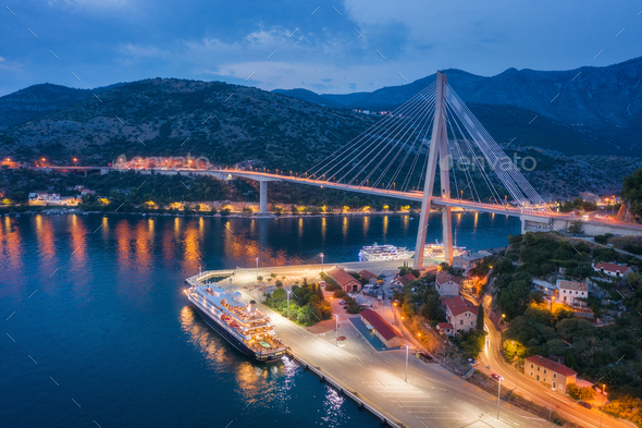 Aerial view of cruise ship at harbor and bridge at night - Stock Photo - Images