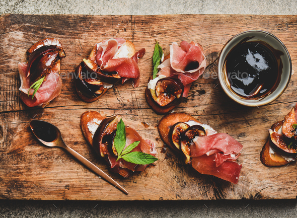 Crostini with prosciutto, cheese and figs on wooden board - Stock Photo - Images
