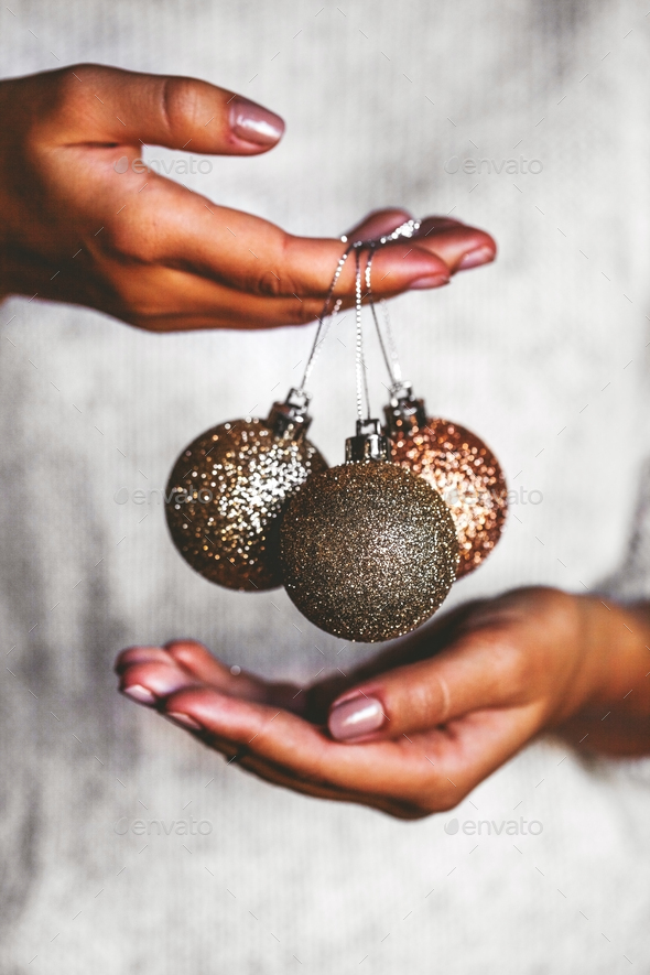Woman in warm sweater holding toys glass decorative balls in hands, copy space. Christmas - Stock Photo - Images