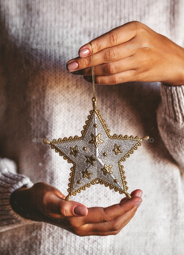 Woman in warm woolen sweater holding toy glass decorative star in hands, copy space, square - Stock Photo - Images