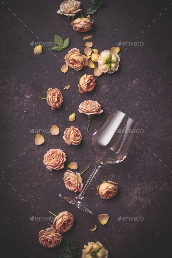 Rose wine and roses on dark purple background, flat lay - Stock Photo - Images
