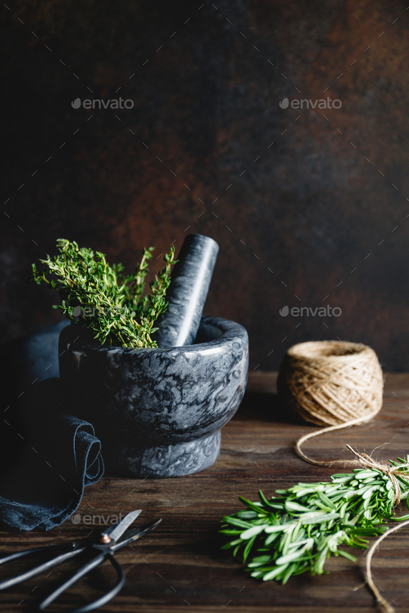 Fresh herbs in a marble mortar on a table - Stock Photo - Images
