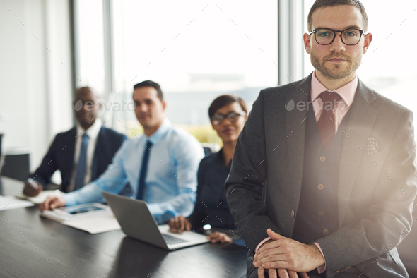 Handsome Caucasian executive with three employees - Stock Photo - Images