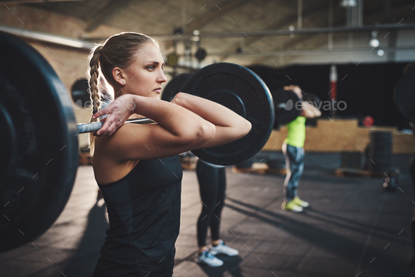 Woman pulling up large barbell in fitness class - Stock Photo - Images