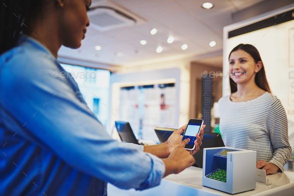 Woman watching customer pay at register with phone - Stock Photo - Images