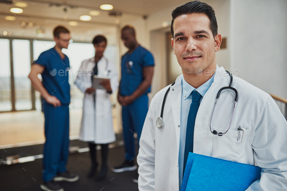 Male doctor with colleagues in background - Stock Photo - Images