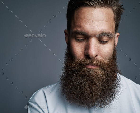 Young man with a long beard deep in thought - Stock Photo - Images